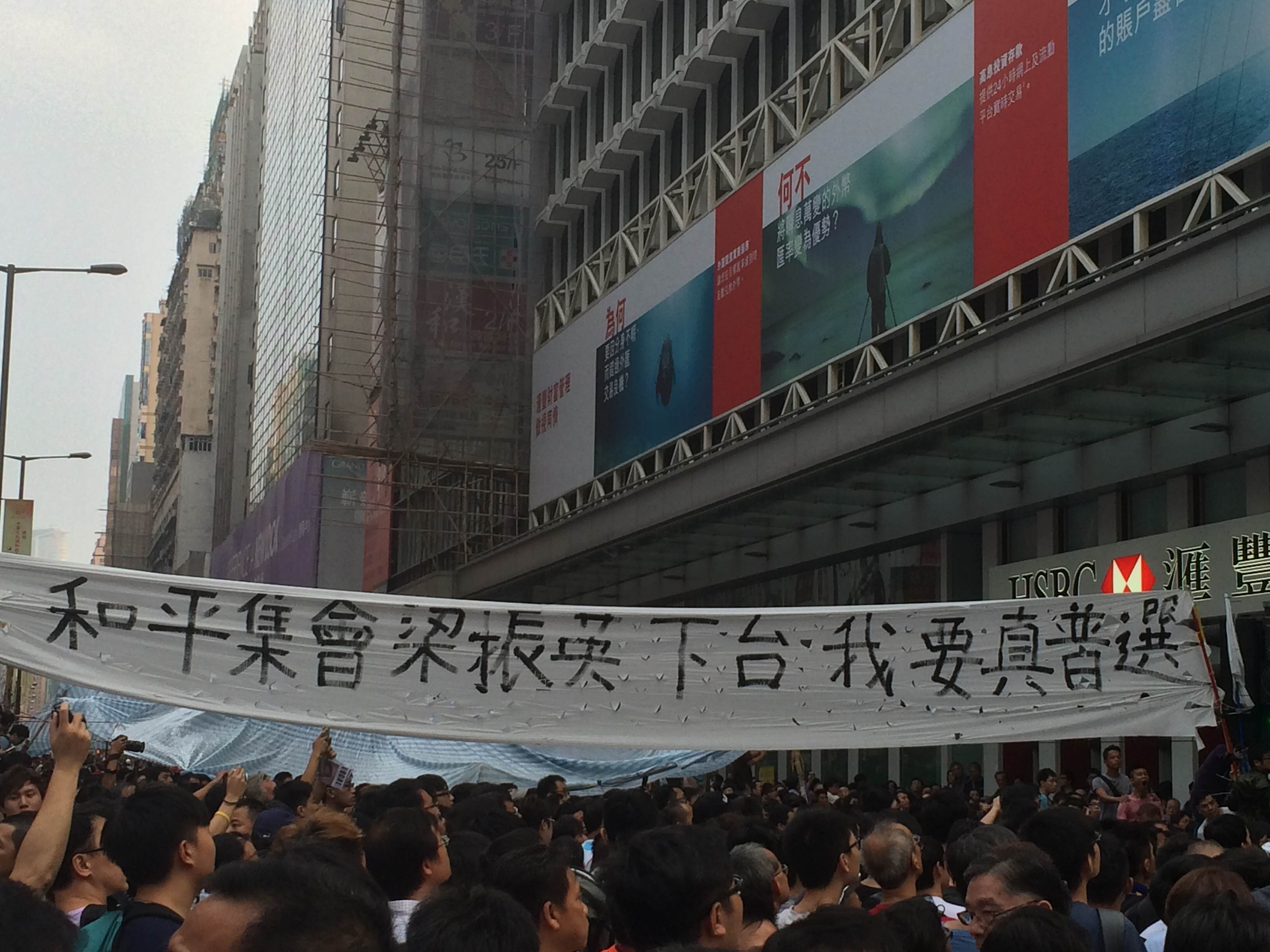 "Protestors with banner that reads ""People of peace unite. We want CY Leung (HK chief executive) to resign"""