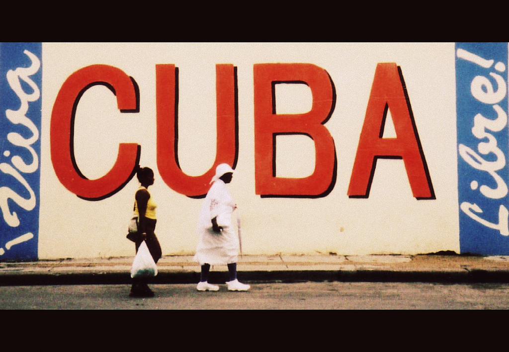 "Two Cuban women walk past a mural on the side of a building reading ""Cuba ¡ Viva Libre!"" (by 'flippinyank' via Flickr)"